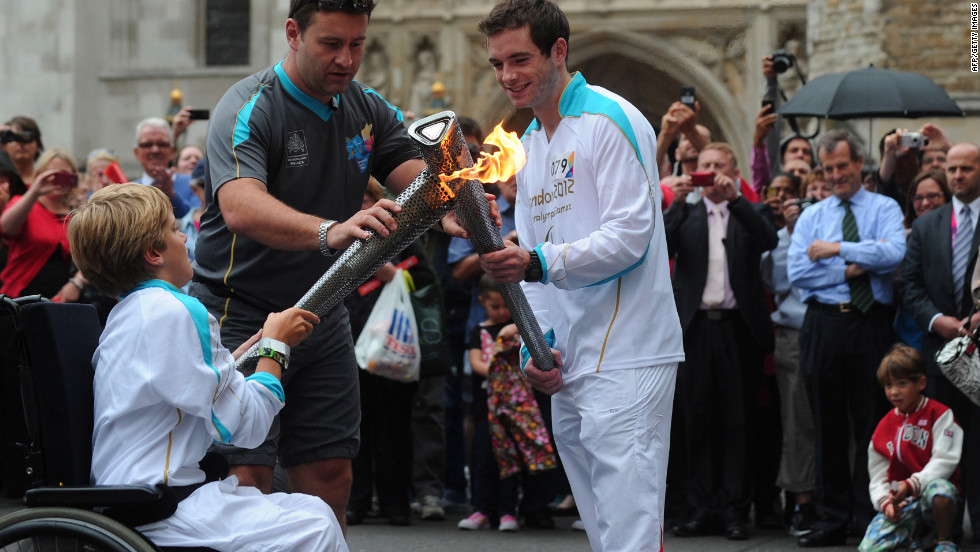 Torchbearers exchange the Paralympic flame outside Westminster Abbey in London on Wednesday, August 29.
