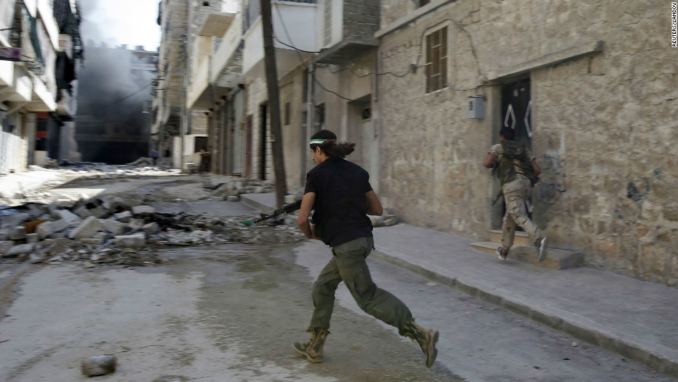 Free Syrian Army rebels dodge fire from Syrian forces as they run down a street in Aleppo on Tuesday.