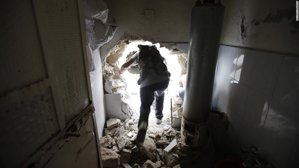 A Free Syrian Army fighter walks through a hole in a damaged house on his way to the El Amreeyeh neighborhood frontline during clashes with government forces in Aleppo.