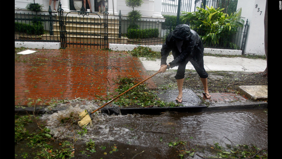 Mark Savoie cleans Espanade Avenue in New Orleans of tree debris to help the area near Burgundy drain as Isaac slowly moves inland.