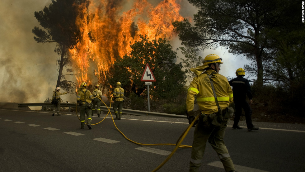 Firefighters try to extinguish wildfires in Ojen, near the town of Malaga, on August 31, 2012. More than 250 firefighters on the ground, backed by eight planes and nine helicopters in the air, battled the blaze after hot, dry winds sent it racing through tinder-dry forest in southern Spain.