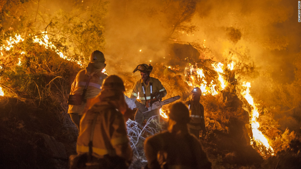 Members of a wildfire brigade try to extinguish a fire in Bedar, a town in the Almeria region of Spain on August 26, 2012. Wildfire has since spread further down the Spanish coast towards Marbella.