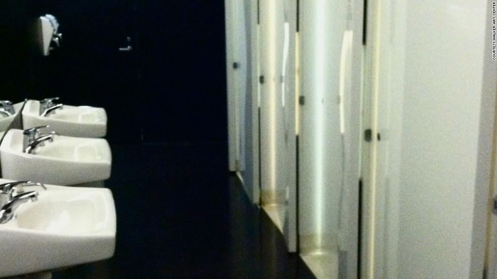 Glossy white doors contrast dramatically with black walls in the Walker Art Center's sleek restrooms.
