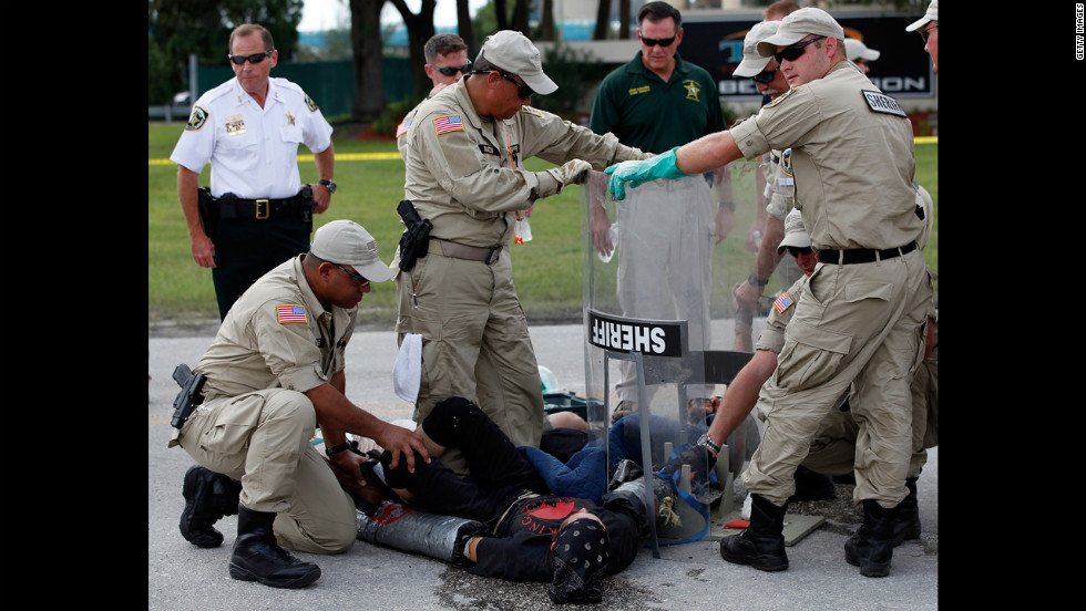 Law enforcement officials work to free protesters with Earth First, who had connected themselves to each other in front of the Big Bend TECO Power Station in Apollo Beach, Florida. Substantially fewer protesters took to the downtown Tampa streets Thursday.