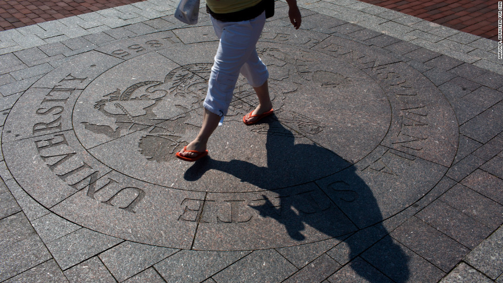 A student traverses the seal of Pennsylvania State University at the center of its University Park campus.