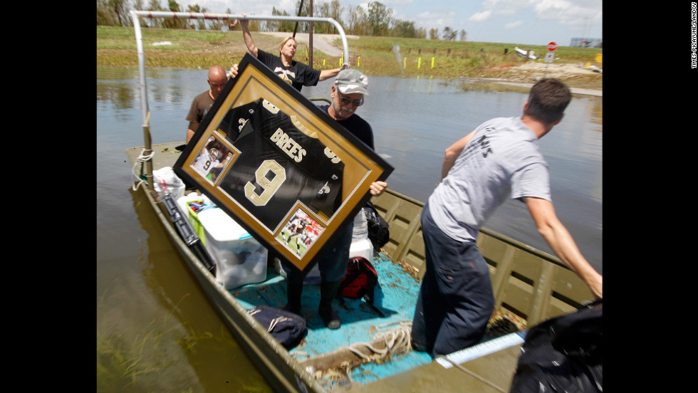Russell Wilson, center, helps to move a water-damaged Drew Brees jersey from his daughter's home in Braithwaite.