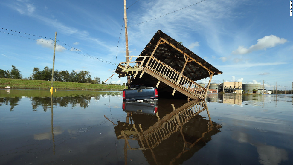 A damaged structure rests atop a partially submerged truck in Braithwaite, Louisiana.