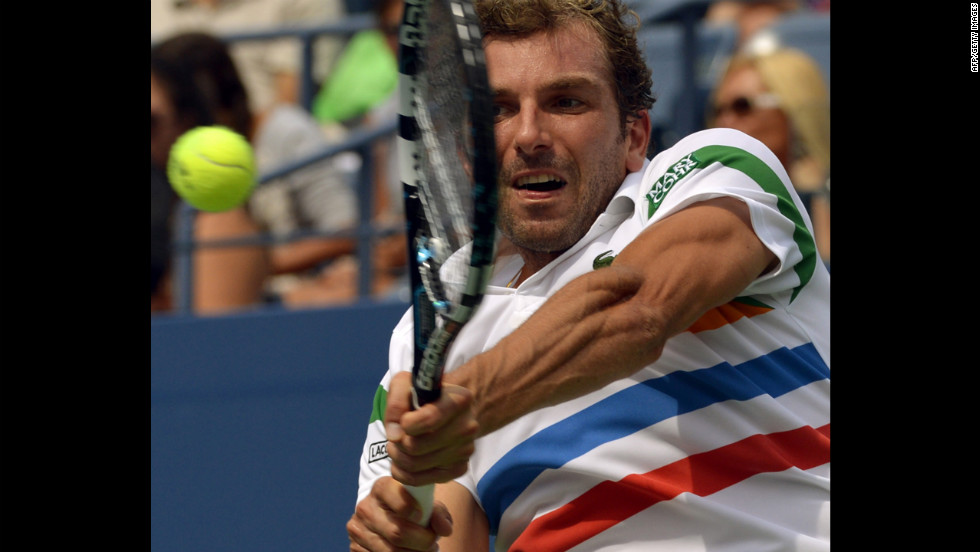 Benneteau returns a shot to Djokovic.
