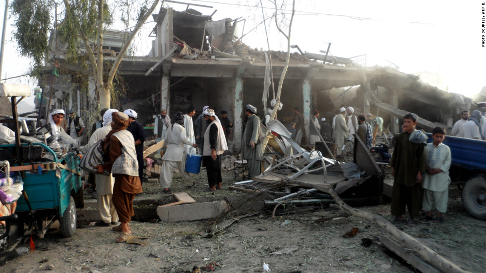 Afghans observe the scene of a recent car bombing in Kandahar. The police chief, Gen. Abdul Raziq, was among 16 people injured in the attack on August 28. Four people were killed.