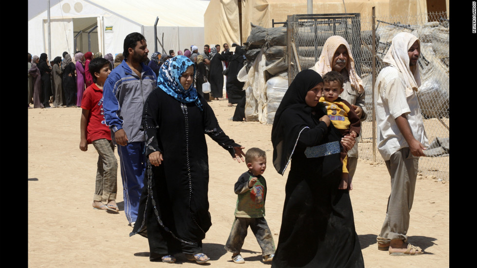Syrian refugees walk through the camp.