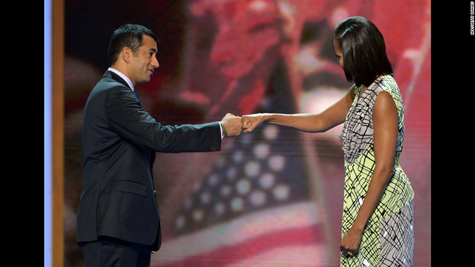 Michelle Obama and actor and former Obama administration aide Kal Penn bump fists after a rehearsal for her speech on Monday.