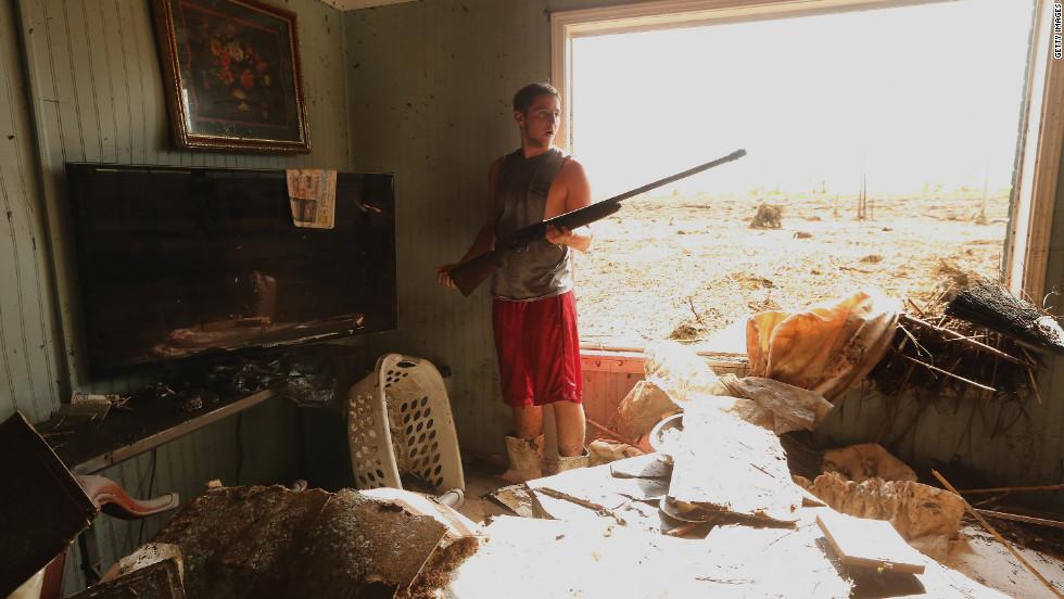 Eric DeSalvo salvages a gun Monday from the flooded Martinez home in Braithwaite, Louisiana.