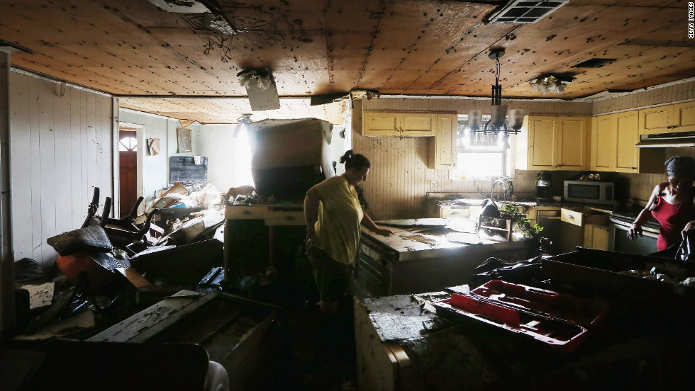 Melanie Martinez, center, and Kala Martinez salvage items from their flooded home on Monday.