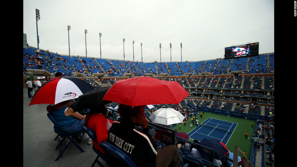 Spectators shelter under umbrellas as rain delays play during the women's singles quarterfinal match between Maria Sharapova of Russia and Marion Bartoli of France on Tuesday.