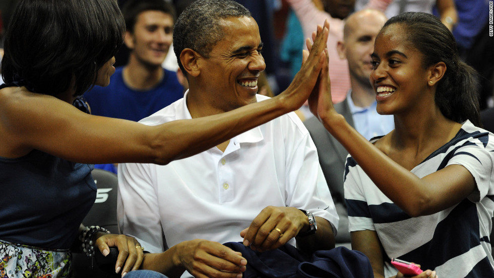 President Obama shares a laugh with his wife and Malia as the U.S. men's basketball team plays an exhibition game in Washington in July 2012.