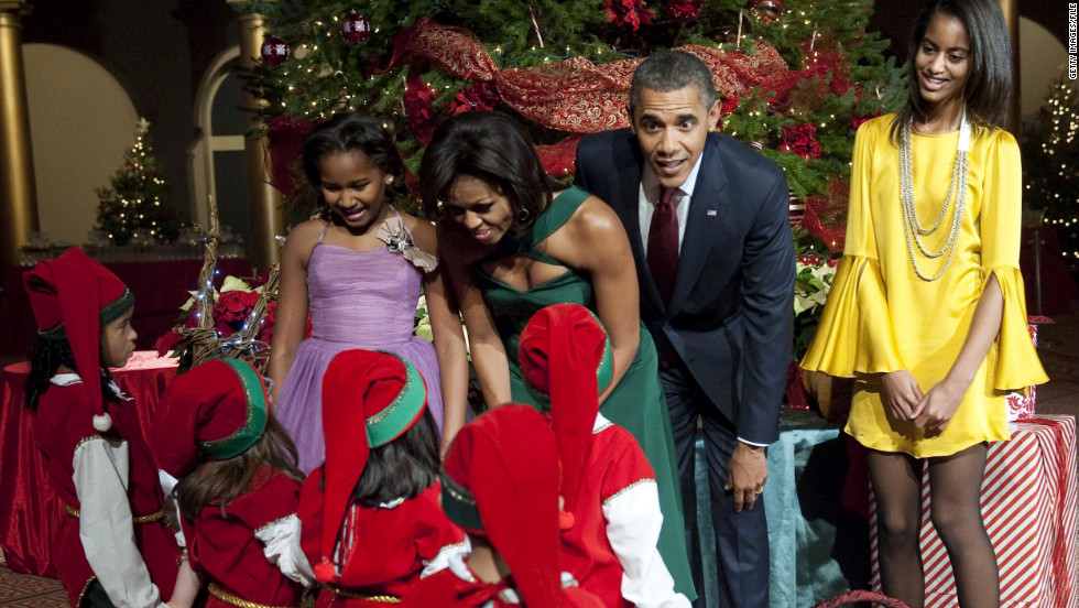 The first family greets children dressed as elves at a museum in Washington in December 2011.