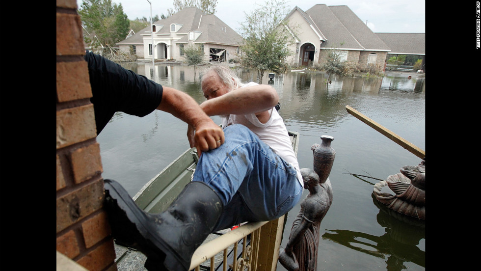 Fred Leslie is helped into a boat by Jesse Shaffer after he and his half-brother made their way to the house to retrieve items on Wednesday. The Braithwaite neighborhood is still under four feet of water eight days after Hurricane Isaac hit.