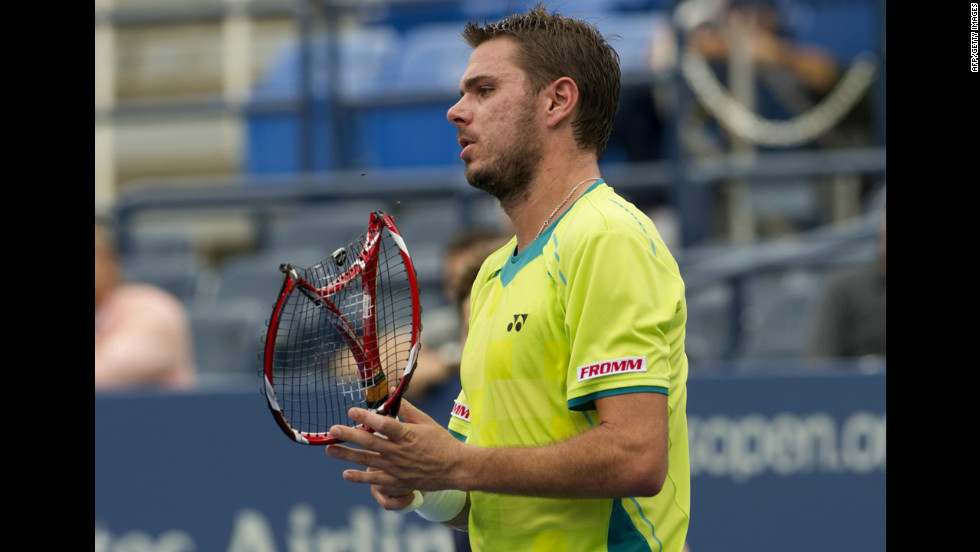 Wawrinka carries his broken racquet off the court during his match on Wednesday against Djokovic.