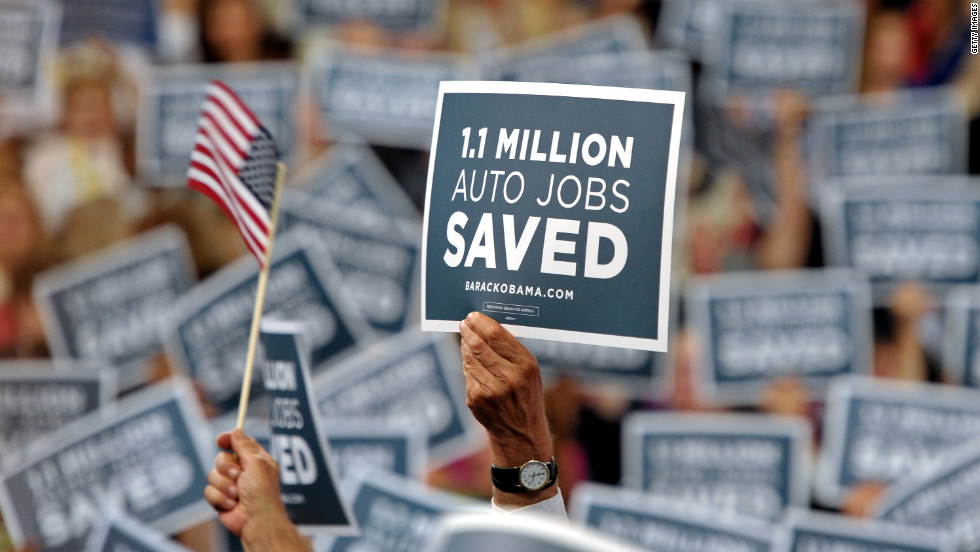 Audience members wave signs Wednesday in support of the American auto industry.