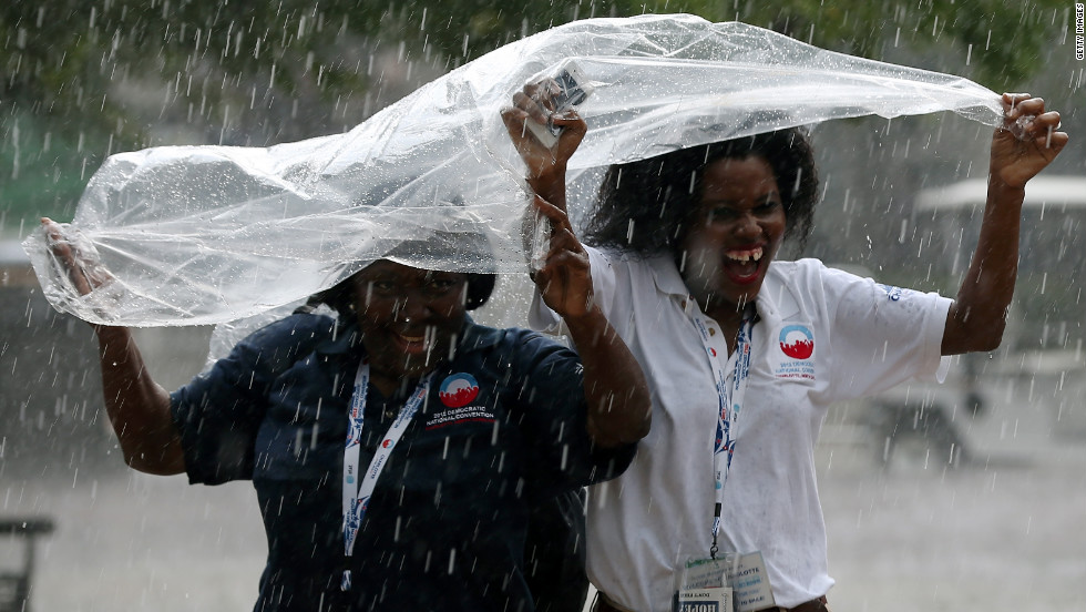 Two women run for cover from the pouring rain during the final day of the convention on Thursday.
