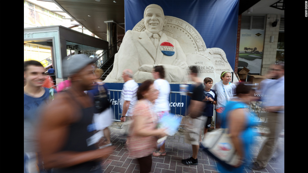 People walk past a sand sculpture of Obama along the streets of Charlotte ahead of the Democratic convention on Monday.