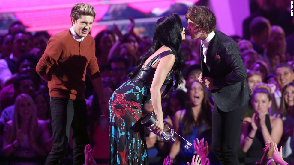 "Singer Katy Perry kisses Harry Styles of One Direction as he and fellow band member Niall Horan accept the award for best pop video for ""What Makes You Beautiful."" The UK boy band took home three Moon Man trophies Thursday night."