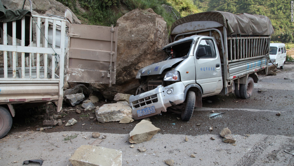 Damaged vehicles sit at a roadside in Yiliang.