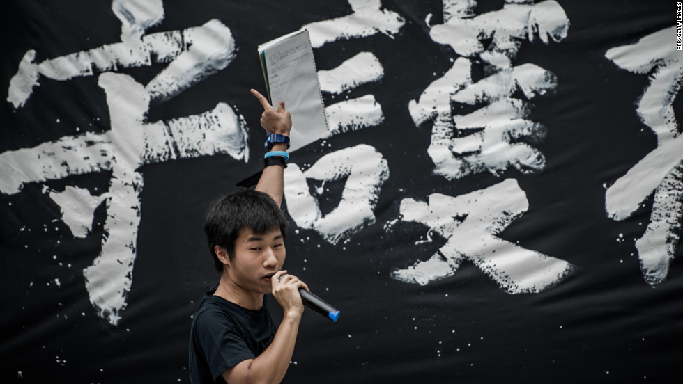 A student addresses a crowd in front of government headquarters in Hong Kong on Friday, September 7 during a protest against plans to introduce Chinese patriotism classes.
