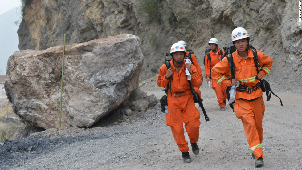 Rescuers walk past a landslide area after a series of earthquakes hit Yiliang County in China's Yunnan Province on Saturday, September 8. Two 5.6-magnitude quakes hit mountainous southwestern China, killing at least 80 people and forcing tens of thousands to leave damaged buildings, state media said.