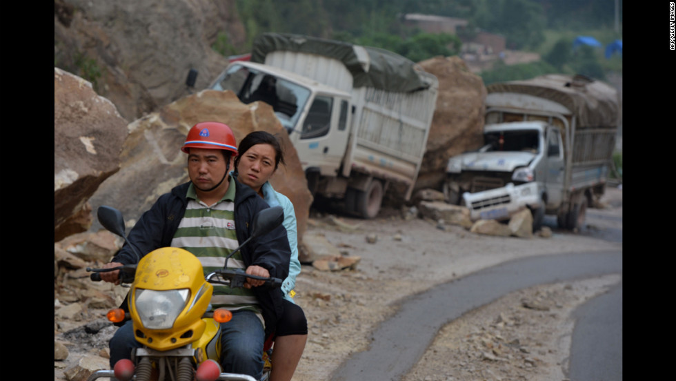 People drive by damaged vehicles that were caught in a landslide on Saturday.