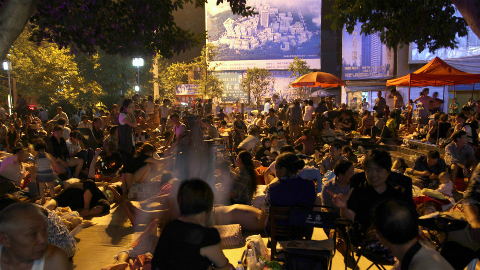 Residents gather to spend a night in the open at the town square in Yiliang.