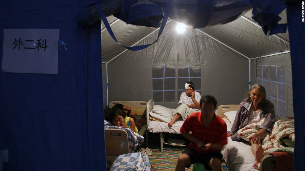Injured residents rest in a makeshift medical tent after being attended to at an emergency relief center set up in the town square in Yiliang on September 8.