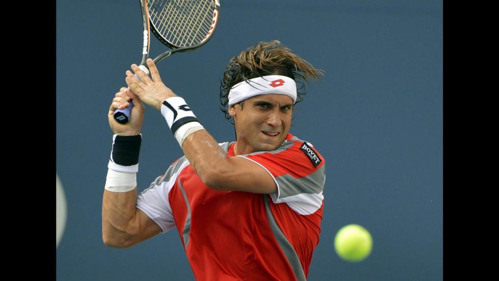 Ferrer follows through his shot  against  Djokovic on Saturday.