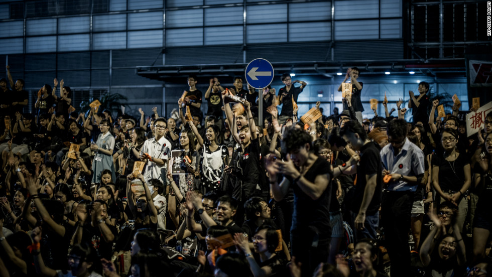 "Protesters shout slogans near the government's headquarters in Hong Kong. They say the ""Moral and National Education"" curriculum amounts to ""brainwashing.""  A booklet called the ""The China Model"" was distributed to schools in July. It said China's ruling party was ""progressive, selfless and united."""