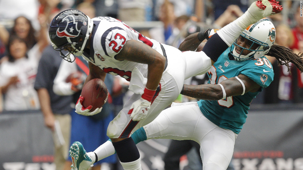No.23 Arian Foster of the Texans leaps over No.30 Chris Clemons of the Dolphins for a touchdown in the second quarter on Sunday.