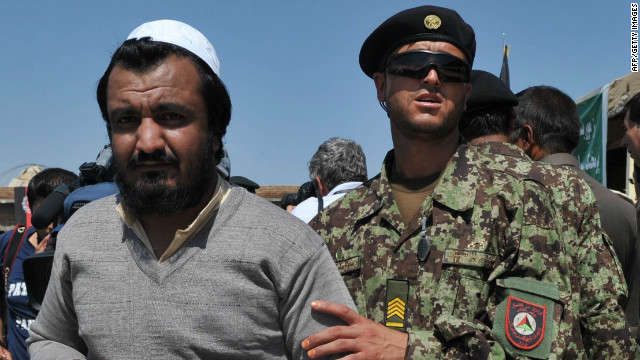 An Afghan National Army soldier escorts a newly-freed prisoner after a ceremony handing over the Bagram prison to Afghan authorities.