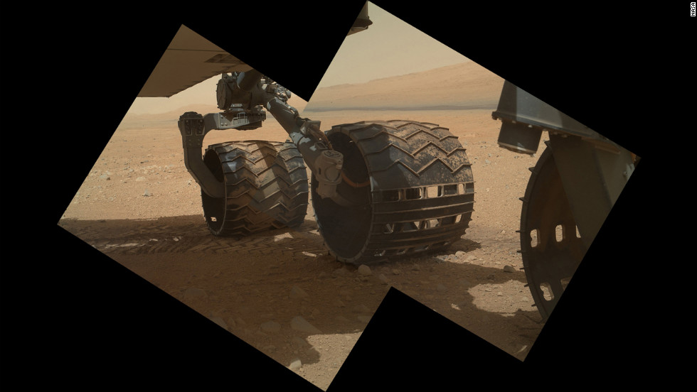 This view of the three left wheels of NASA's Mars rover Curiosity combines two images that were taken by the rover's Mars Hand Lens Imager on September 9, 2012, the 34th day of Curiosity's work on Mars. In the distance is the lower slope of Mount Sharp.