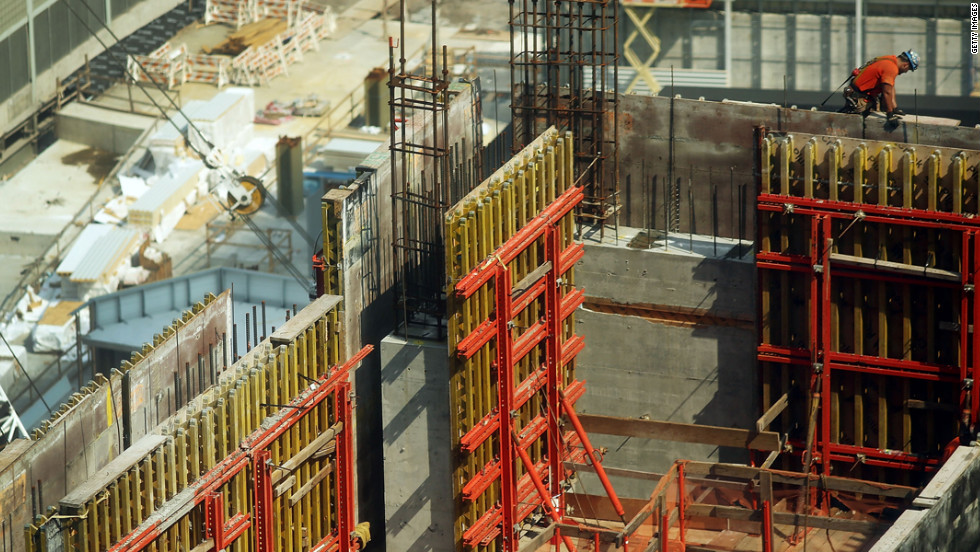 Construction workers continue to work on one of the four office towers being built on the site on Friday.