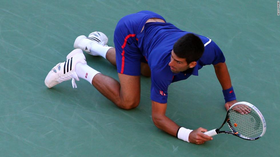 Novak Djokovic drops to the floor as he returns a shot on Monday.