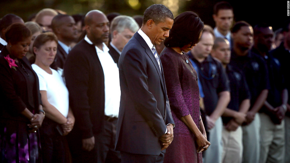 President Barack Obama and first lady Michelle Obama observe a moment of silence with White House staff on Monday.