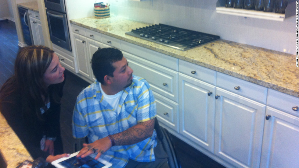 Dominguez explores the automated kitchen in his new 'smart' home with Danielle Tocco of Standard Pacific Homes. The home is controlled by an iPad, with which Dominguez can move cabinets and access the security system and air conditioning.
