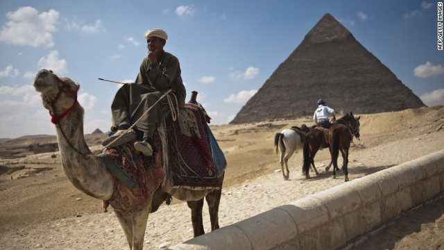 An Egyptian man waits for tourists to take them on camel rides at the Giza pyramids on the outskirts of Cairo on February 14, 2011.