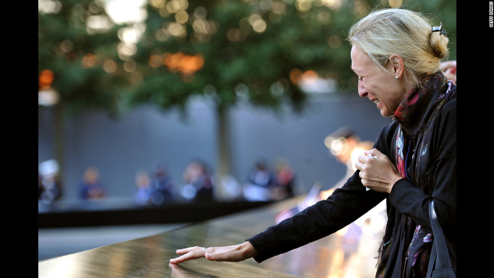 A woman cries as she stands over the reflecting pool at the World Trade Center site on Tuesday.