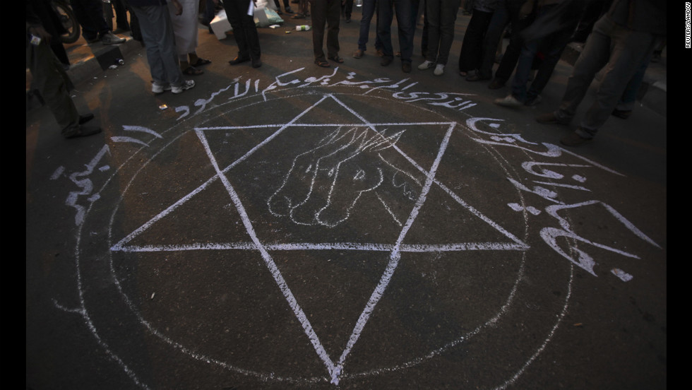 "People stand around a drawing that says ""Remember your black day 11 September"" during the protest in Cairo."