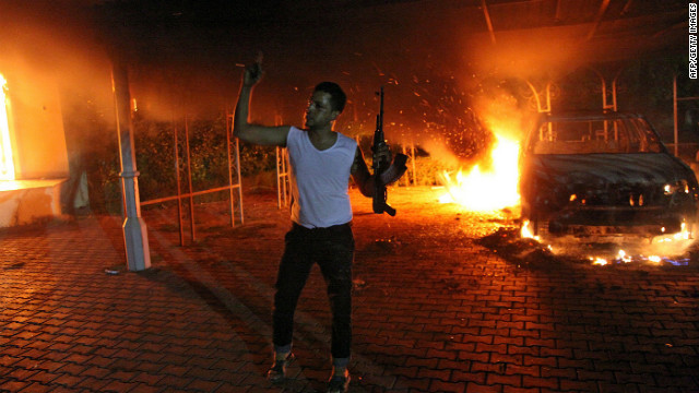 A man waves his rifle as buildings and cars are engulfed in flames at the U.S. consulate in Libya on September 11.