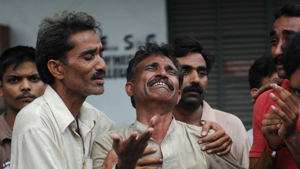 A Pakistani man mourns the death of relatives. Video broadcast by Geo TV showed large crowds of anxious people outside the smoldering building.