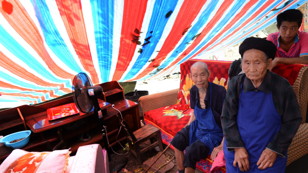 Elderly members of the Peng family sit in their makeshift shelter on Monday after their home was badly damaged.