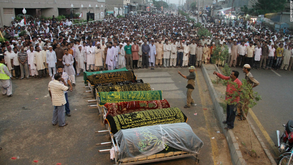 Pakistani Muslims offer funeral prayers of at least 289 garment factory workers who were killed after fire engulfed the building in Karachi.