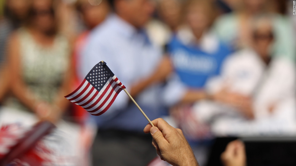 A Mitt Romney supporter waves a flag during his speech at Van Dyck Park in Fairfax, Virginia, on Thursday, September 13.