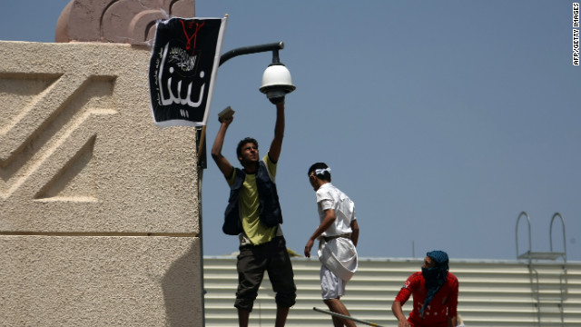 Yemeni protesters try to break the security camera of the US embassy in Sanaa during a protest over a film mocking Islam on September 13, 2012. Yemeni forces managed to drive out angry protesters who stormed the embassy in the Yemeni capital with police  firing warning shots to disperse thousands of people as they approached the main gate of the mission.   AFP PHOTO/MOHAMMED HUWAIS        (Photo credit should read MOHAMMED HUWAIS/AFP/GettyImages)